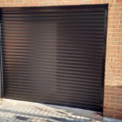 Alluguard 77 Black Rollershutter garage door with Black UPVC reveal liners