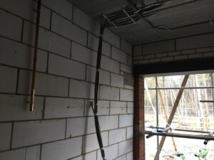 Garage interior with pipes and wiring attached to the walls