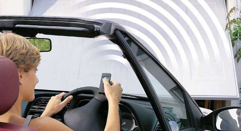 Woman driving convertible car approaching automatic garage door with remote control in her hand