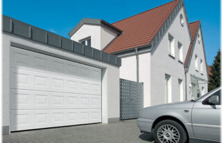 Sectional Garage Doors - White panelled double garage door with car parked in front